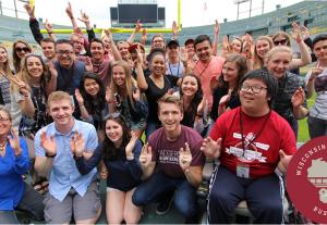 Wisconsin experience bus trip group photo at football stadium.