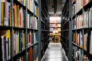 Student studying in the memorial library stacks.