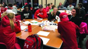 Student athletes gathered around a table in discussion.